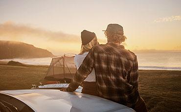 Par sitter på motorhuven och tittar ut mot havet i solnedgången